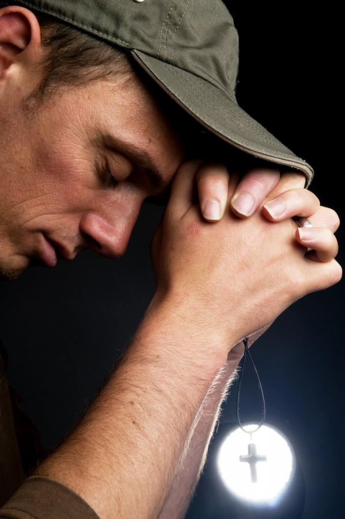Praying Man Holding A Cross